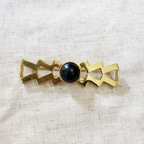 broche dorado y negro